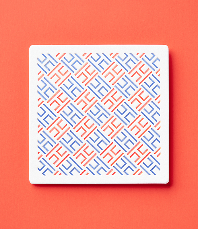 Henrickson Architecture coaster on orange background.