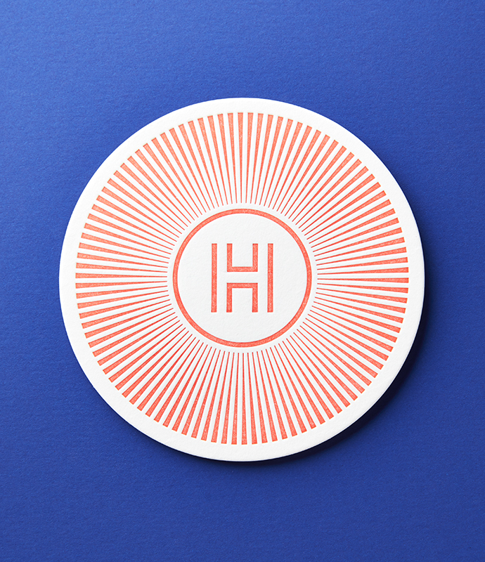 Orange Henrickson Architecture coaster on blue background.