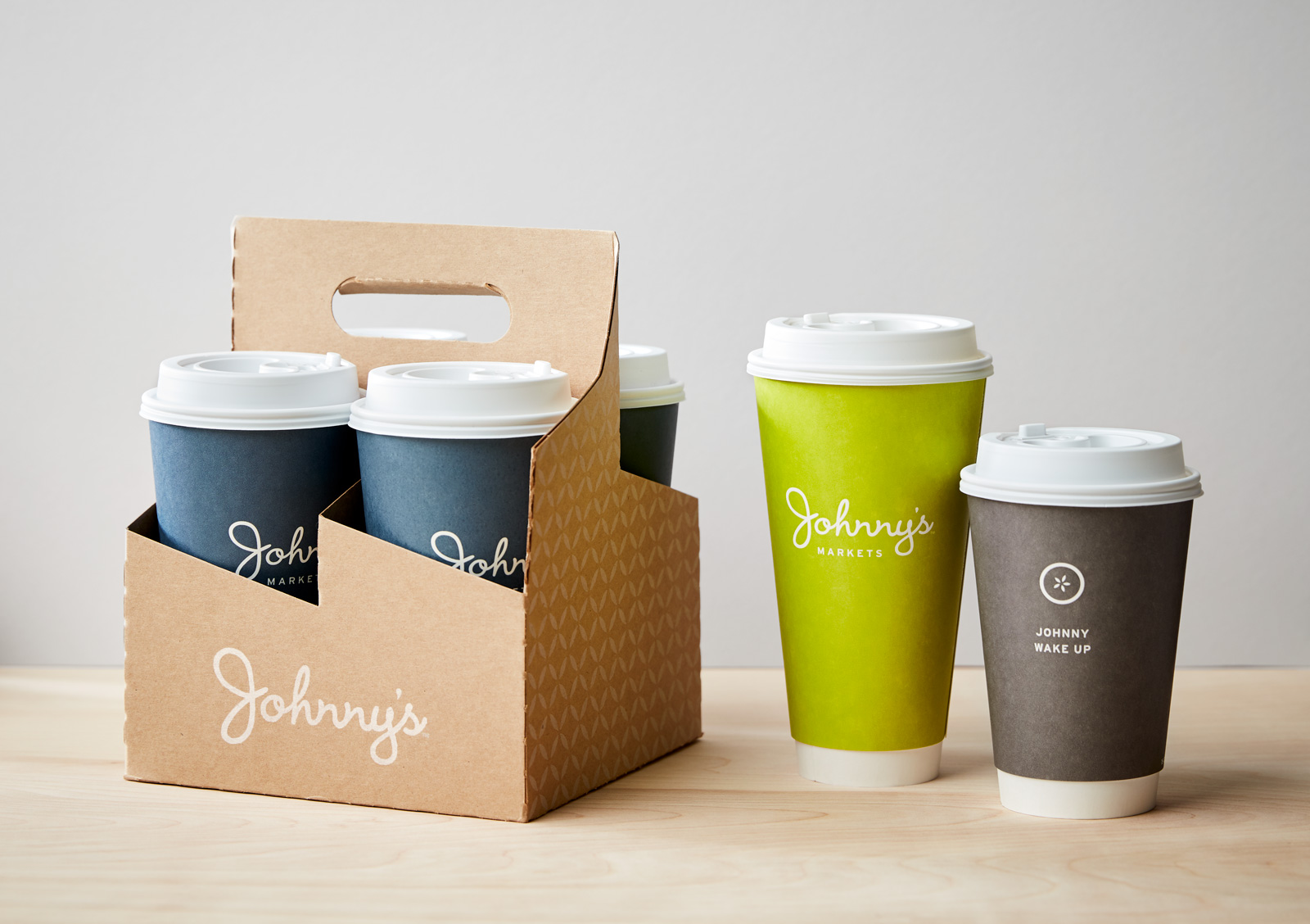 Johnny's Markets coffee cups in a kraft carrier container.