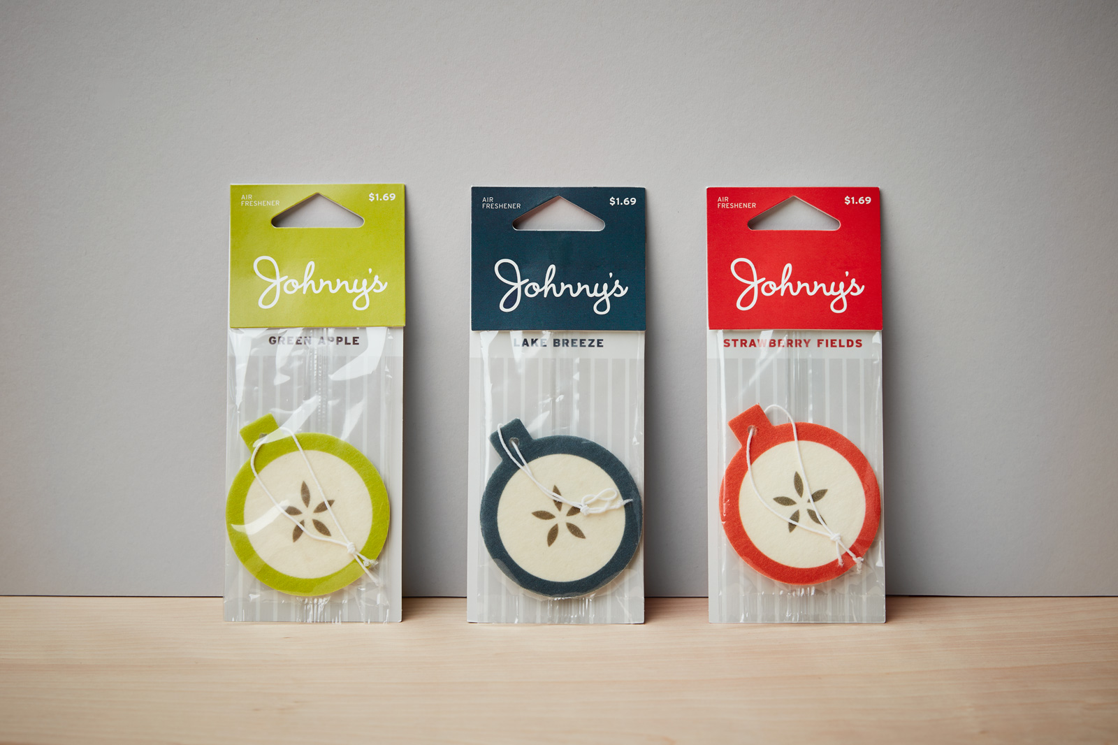 Set of three Johnny's car air fresheners in green (green apple), blue (Lake Breeze) and red (strawberry fields).