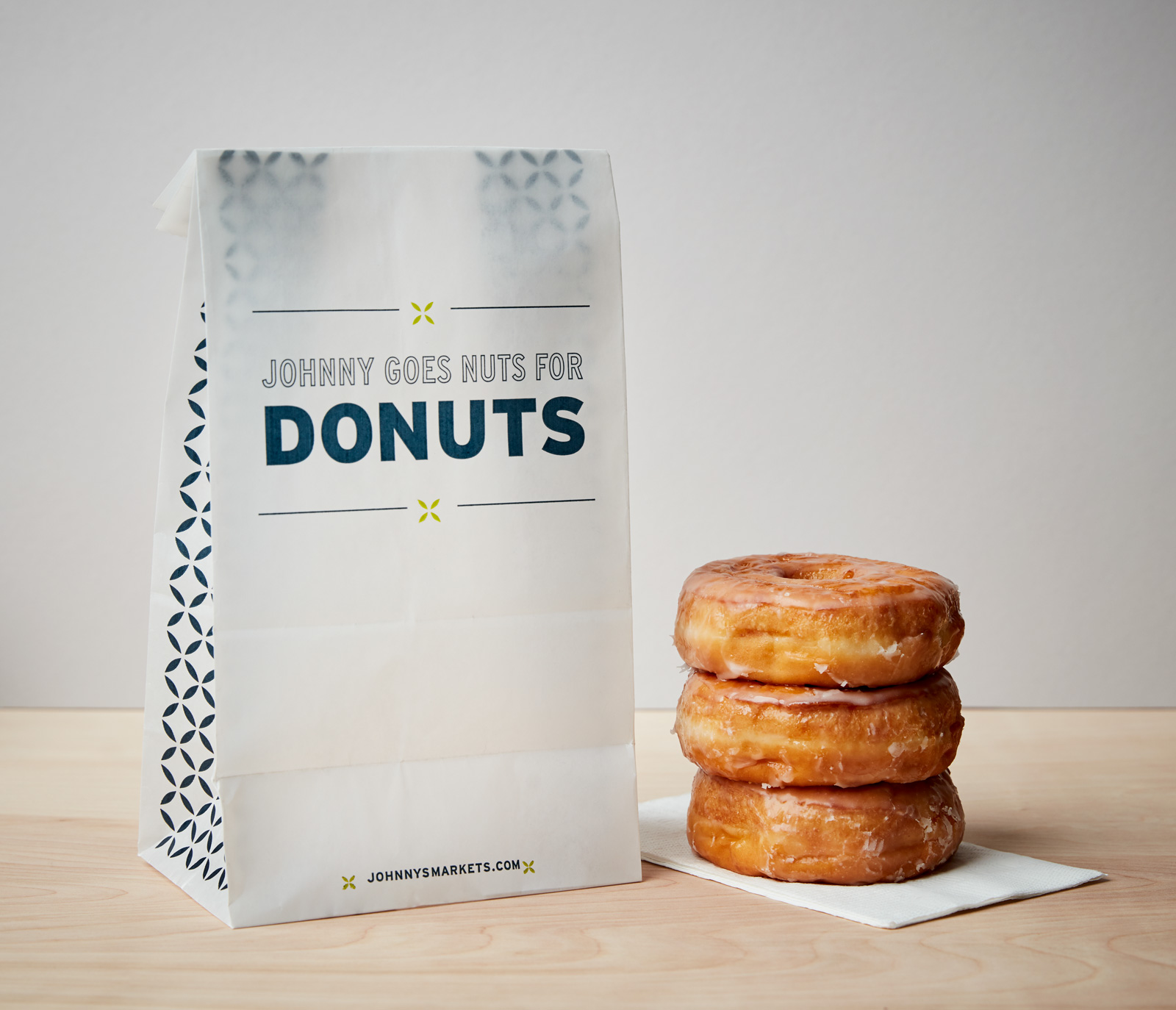"Stack of three glazed donuts next to the bag that reads, ""Johnny goes nuts for donuts."""