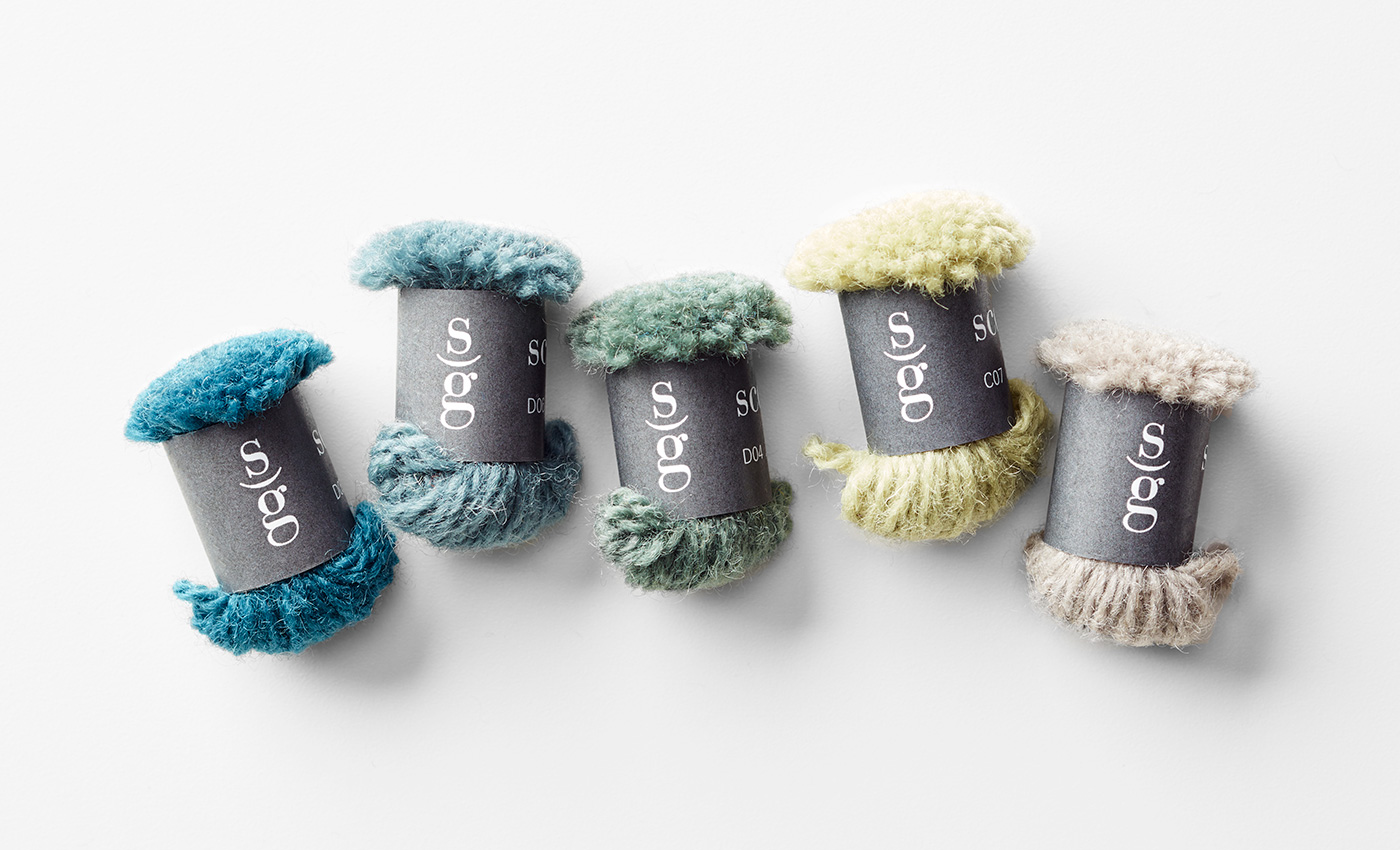 Five colorful yarn poms