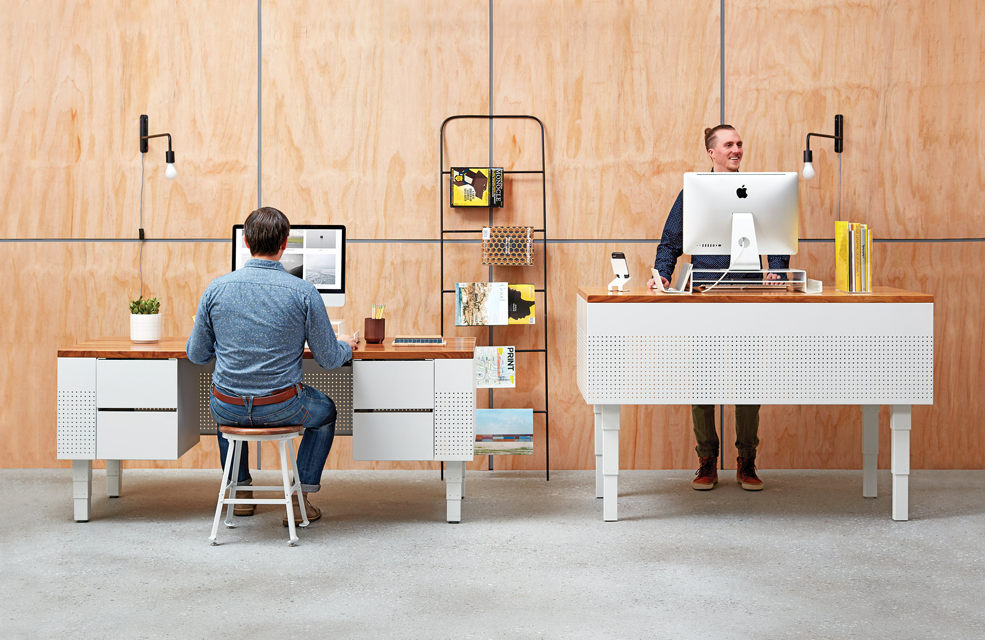 Two men sitting and standing at desk.