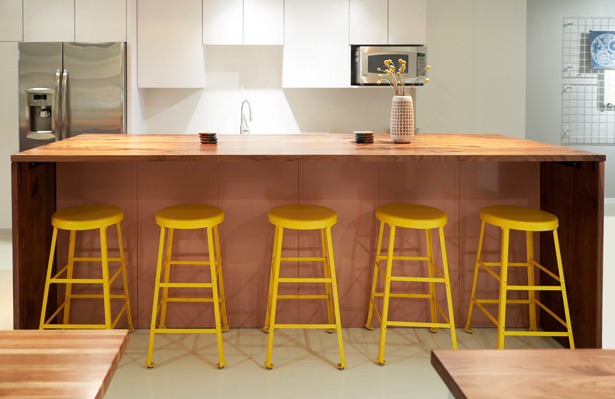 Yellow stools under pink table.