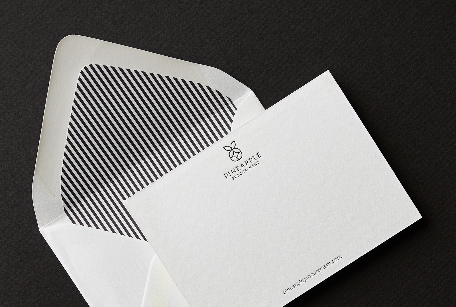 A white Pineapple Procurement notecard shown with an open envelope with a stripe pattern on the inside flap.