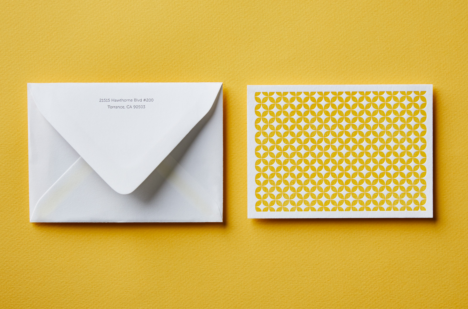 A bright yellow background with a letterpressed, patterned notecard and white envelope