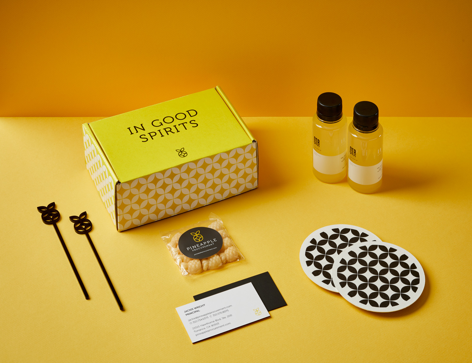 "A yellow box that reads, ""In Good Spirits"",with white pattern, showing the packaging for a box of goodies from Pineapple Procurement. The set includes two mini cocktail bottles, two coasters, a box of pineapple candy and a business card."